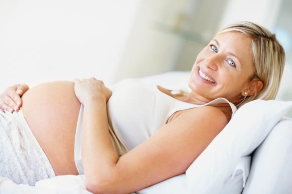 Portrait of a beautiful middle aged pregnant female smiling on the couch